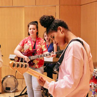 Dacodis Hughes, foreground, works out a bass line with her bandmates during a Girls Rock! Indianapolis rehearsal in the bottom floor of the Informatics and Communications Technology Complex. Photo by Tim Brouk, IU Communications