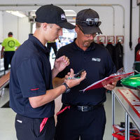 IUPUI student Isaac Atkinson looks over data with IndyCar technical director Kevin Blanch in the tech inspection area on a morning before Indianapolis 500 practice. Liz Kaye/IU Communications.