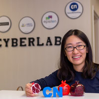 Alice Zhou, associate director of CyberLab, poses with plastic pomegranates in the lobby of CyberLab. Various versions of the fruit can be found around the lab, as it was an inspiration and an incentive tool used in CourseNetworking, one of the lab's software successes. Photo by Liz Kaye, Indiana University