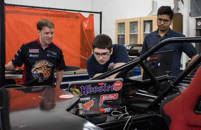 From left: Tyler Stover and students Alan Orr and Somesh Rath work on the IUPUI engineering motorsports' Mazda Miata race car in one of the program's garages. Photo by Chris Meyer, IU Communications