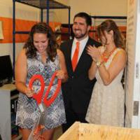 Jenn Boldig, left, Joe Spaulding and Erin Sass cut a ribbon to open the food pantry